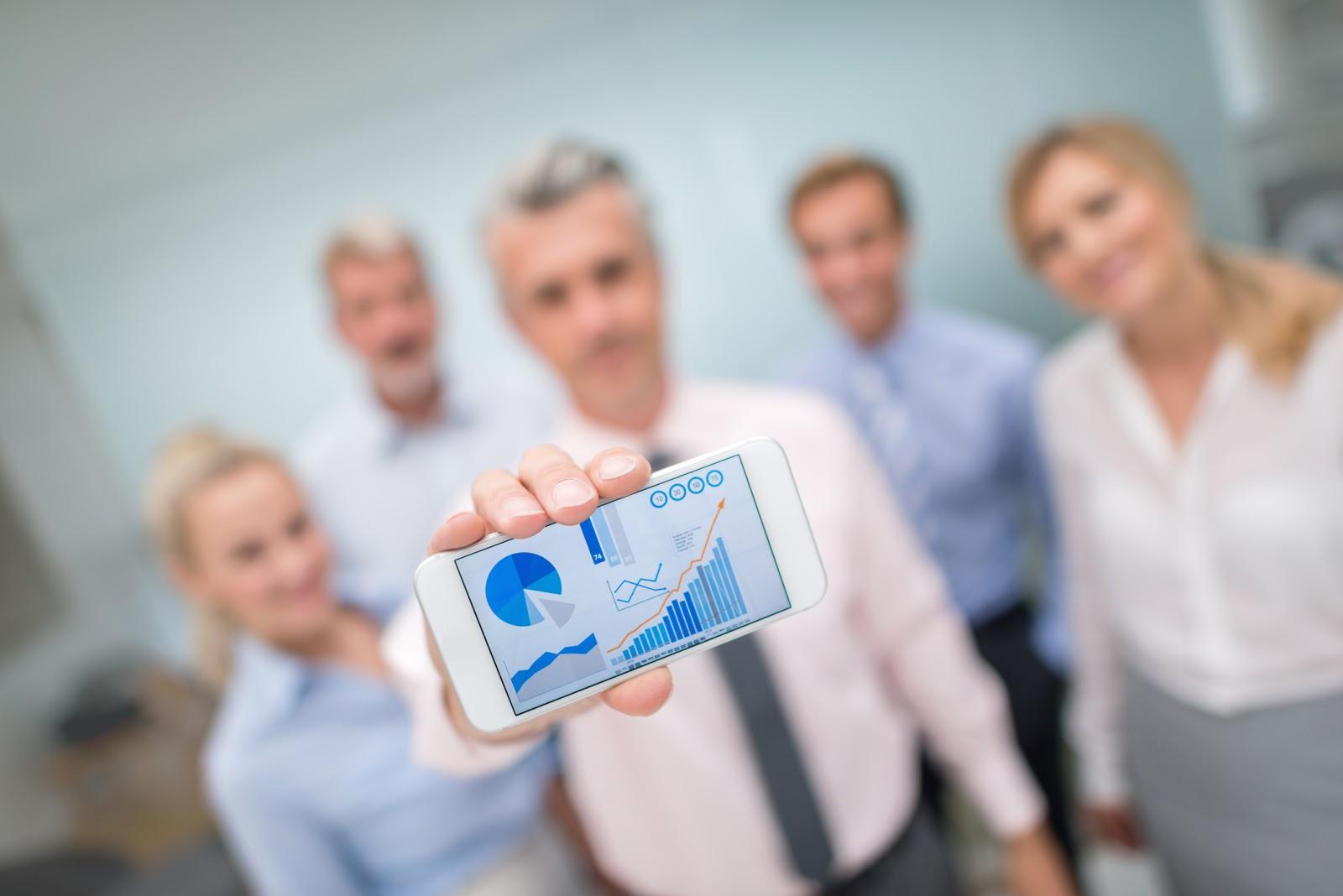 financial advisors showing digital marketing graphs on mobile phone