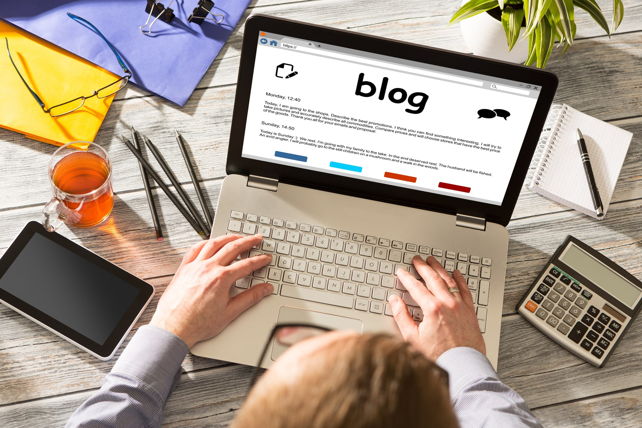financial advisor sitting at a desk typing a blog article into his open laptop computer