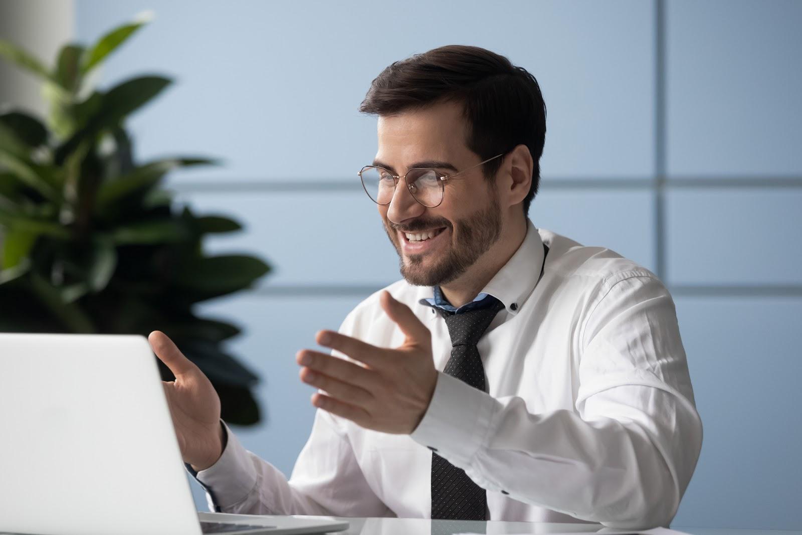 man speaking to computer conducting webinar