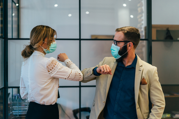 financial advisors wearing face masks touching elbows instead of shaking hands due to the COVID-19 pandemic