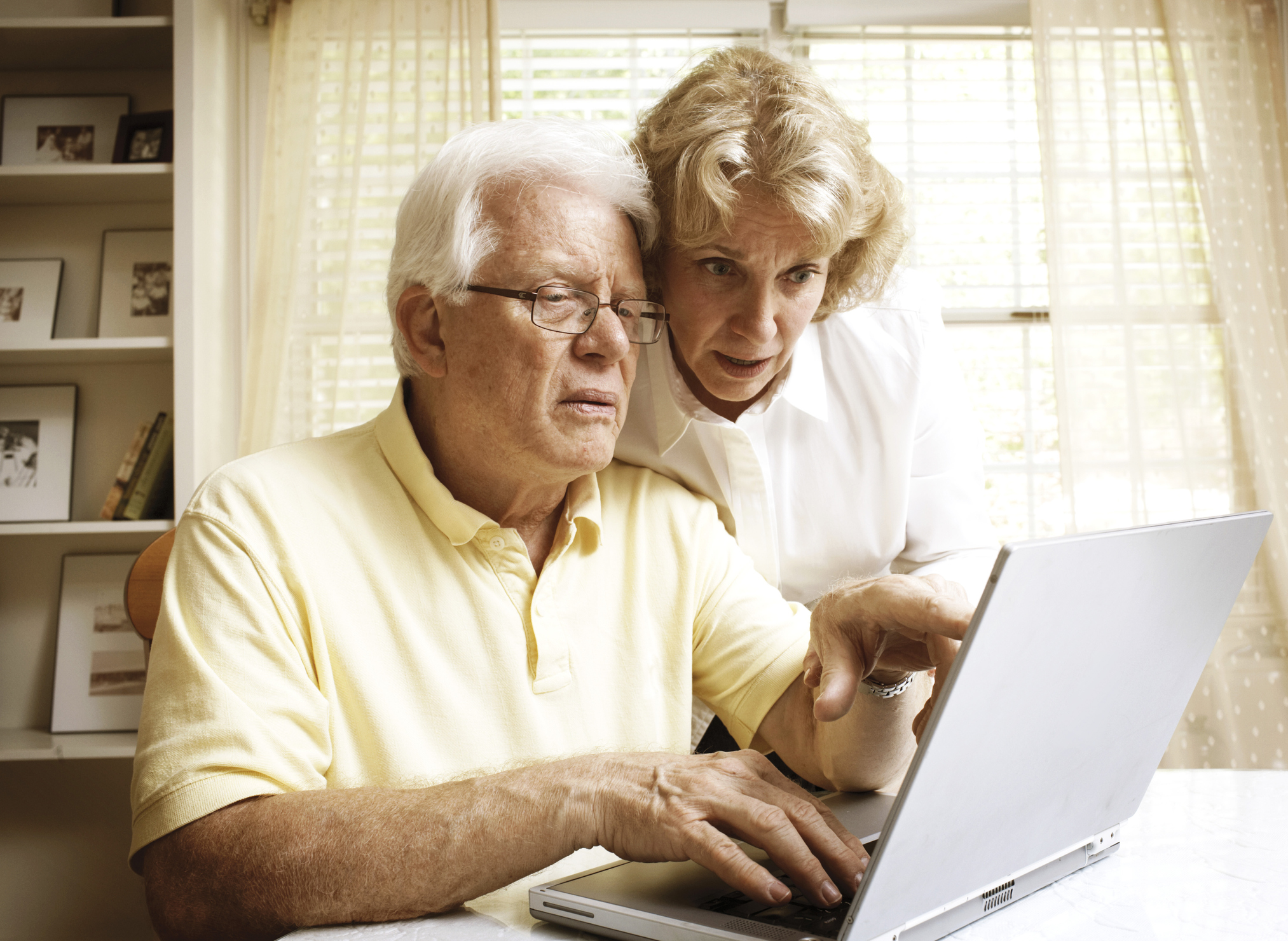 older couple practicing social distancing by using their computer to research financial advisors