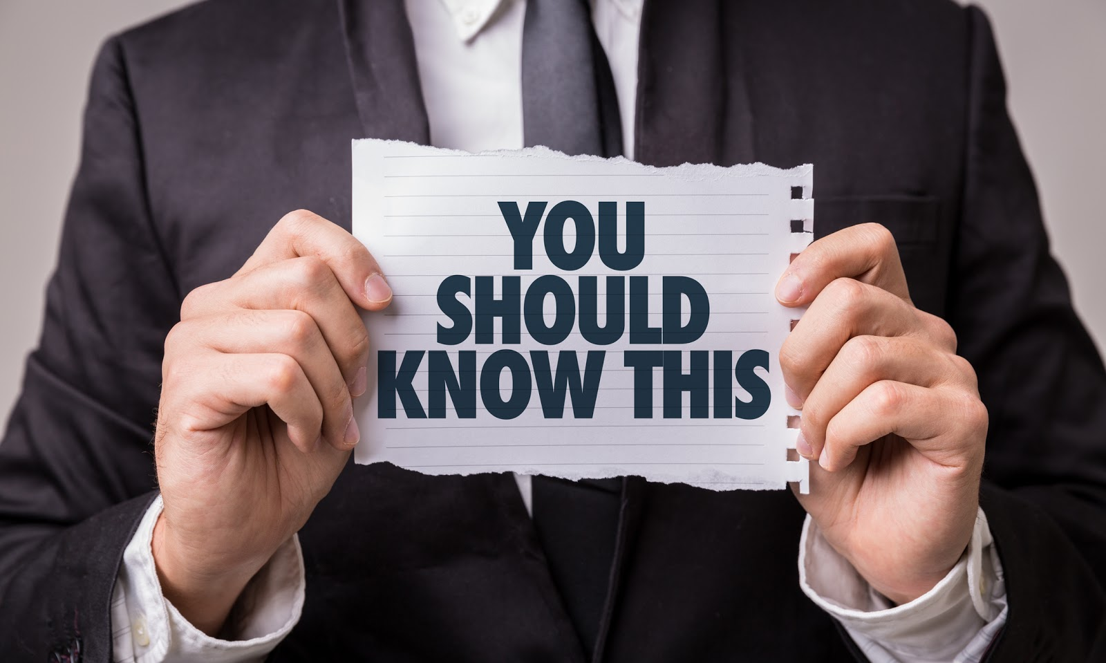 closeup of man holding paper saying You Should Know This