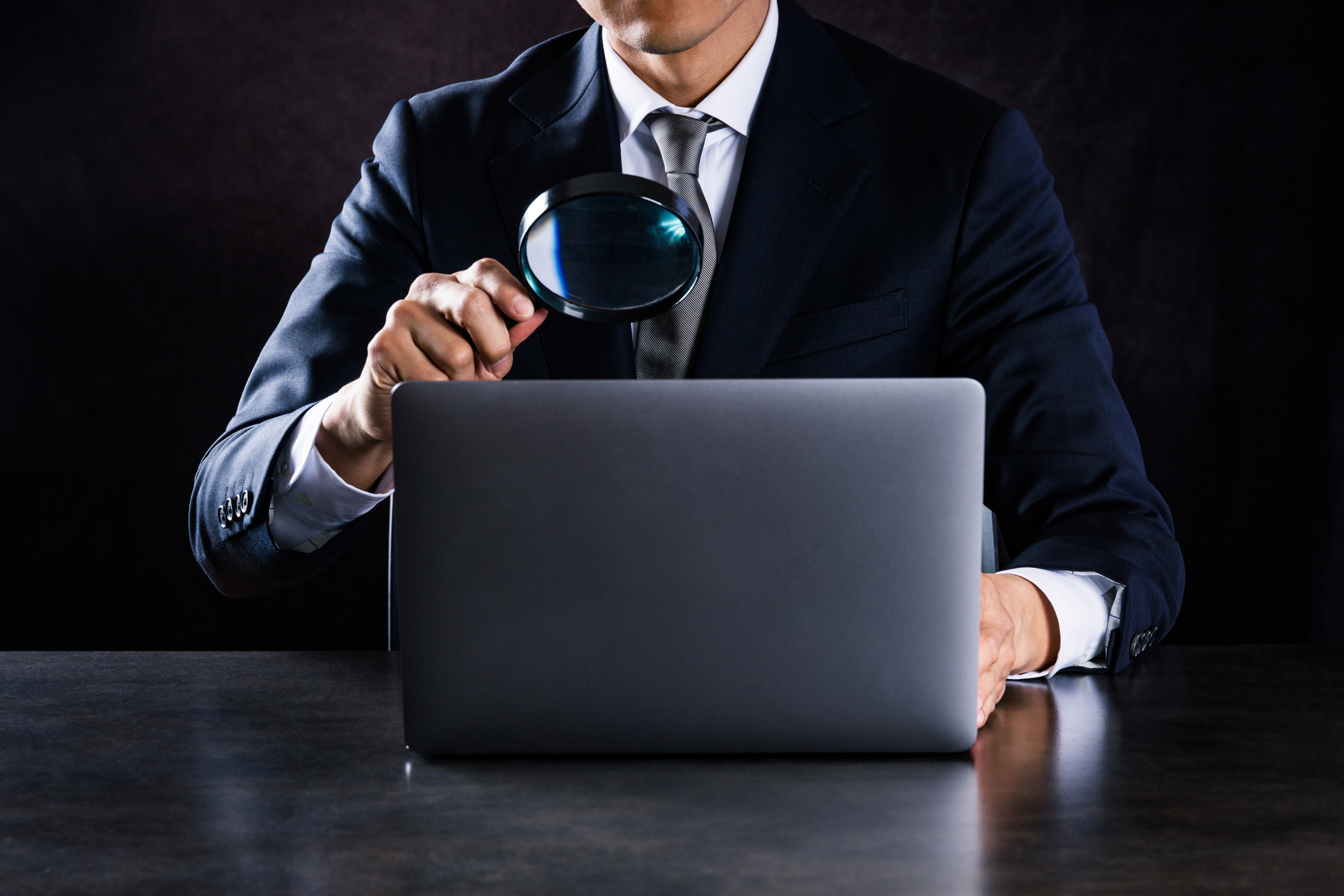 financial advisor wearing a suit and tie looking at an open laptop screen showing the best financial advisor website