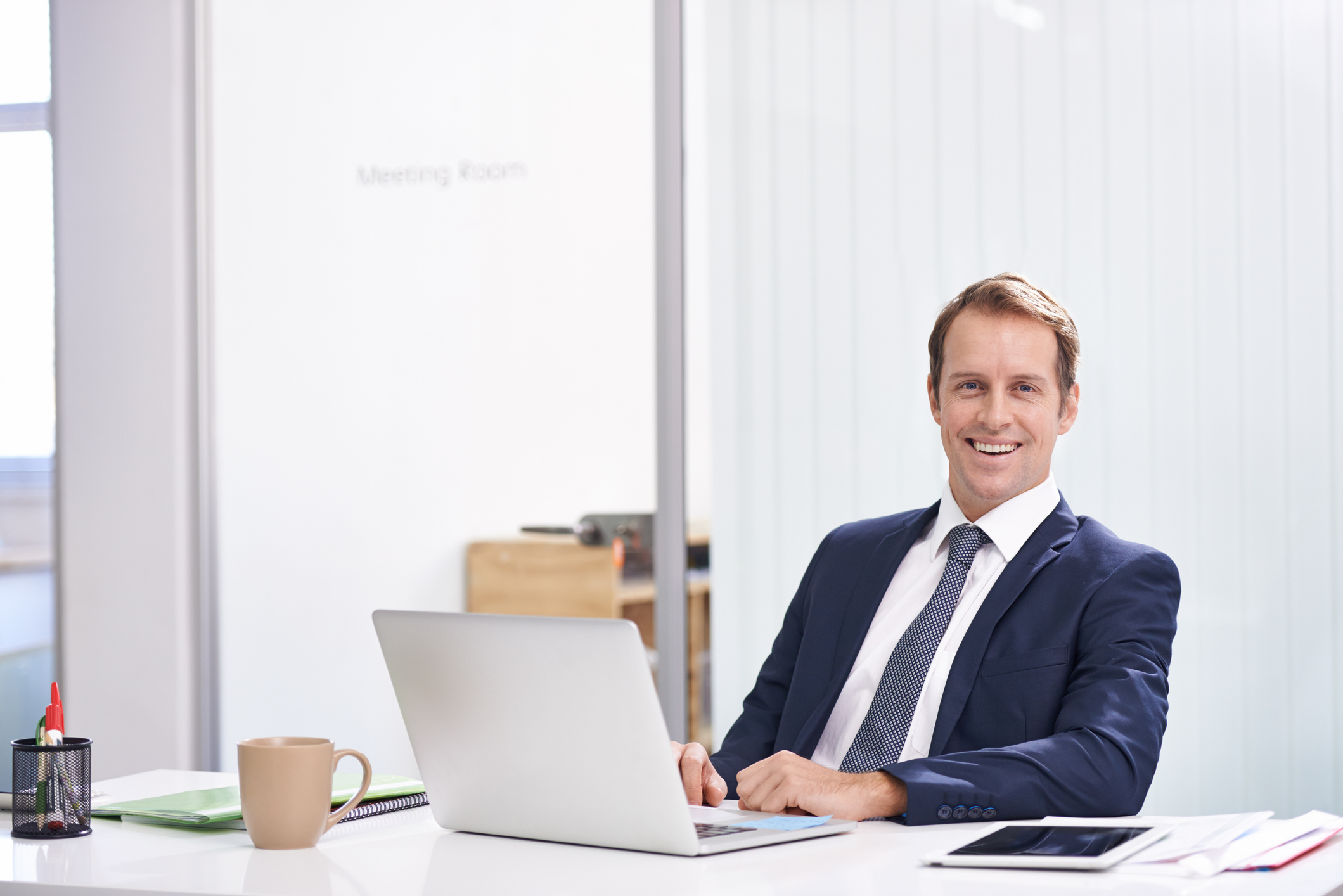 financial advisor sitting at desk in front of open laptop using digital marketing to get new clients